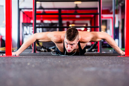 fitness center: Man exercising doing push-up on floor of sport fitness gym Stock Photo