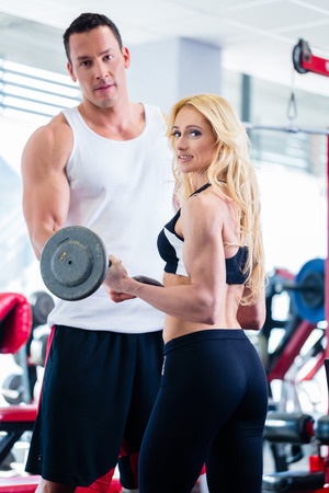 assisted: Woman in gym training for body building competition with barbell assisted by personal fitness trainer