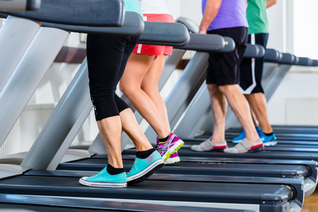 Group of people in gym on treadmill running, only legs to be seen photo