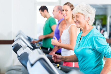 exercising: Group with senior and young men and women on treadmill in fitness gym running for sport Stock Photo