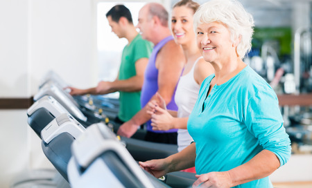 Group with senior and young men and women people on treadmill in fitness gym running for sport photo