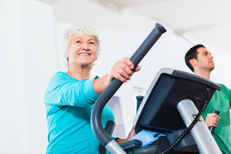 damas antiguas: Mujer mayor en el entrenador el�ptico ejercicio de gimnasio Foto de archivo