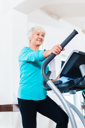 eliptica: Mujer mayor en el entrenador el�ptico ejercicio de gimnasio Foto de archivo