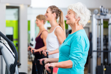 elderly exercise: Senior and young people on vibrating plates in gym doing fitness exercise