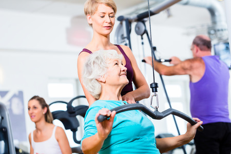 old center: Senior woman doing back training with trainer in gym at machine Stock Photo