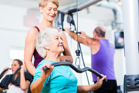 senior exercising: Senior woman doing back training with trainer in gym at machine Stock Photo