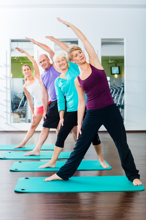 Exercising: Group of senior people and young woman and men in fitness gym doing gymnastics