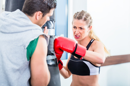 Young woman with trainer in boxing sparring hitting sandbag Stock Photo