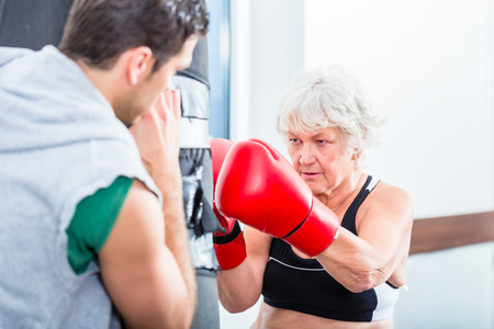 sandbag: Senior woman with trainer in boxing sparring hitting sandbag