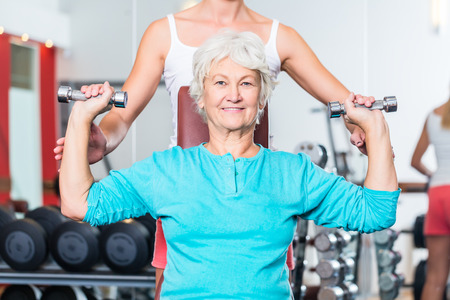 pectoral: Senior women with fitness trainer in gym lifting dumbbell for pectoral training as sport exercise