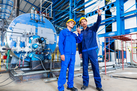 manufacturing equipment: Worker in Asian manufacturing plant discussing in front of machines Stock Photo