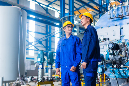 machines: Worker in Asian manufacturing plant discussing in front of machines Stock Photo