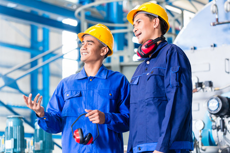 metalworker: Worker in Asian manufacturing plant discussing in front of machines Stock Photo