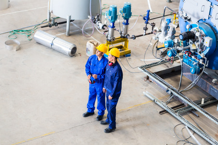 metal worker: Two workers in industrial factory discussing in front of machines, top view on the men Stock Photo