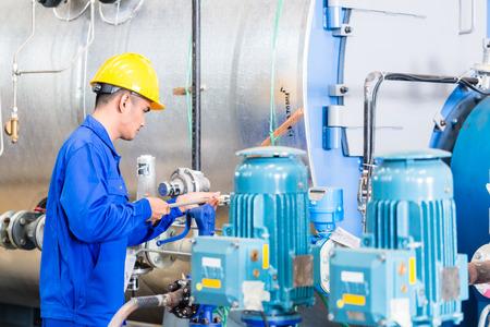 mecanica industrial: T�cnico en f�brica asi�tica en mantenimiento de la m�quina de trabajo con la llave