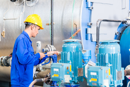 Technician in Asian factory at machine maintenance working with wrench Standard-Bild