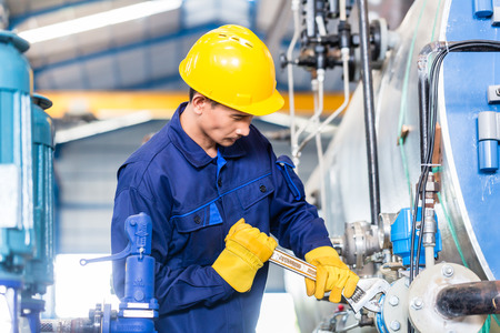 Technician in Asian factory at machine maintenance working with wrench Stockfoto