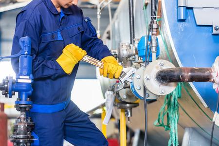mecanica industrial: T�cnico en mantenimiento de la m�quina en la f�brica trabajando con la llave Foto de archivo