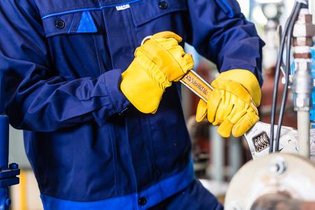 Technicus in de fabriek bij onderhoud van de machine werken met moersleutel