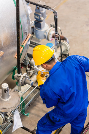 manufacturing equipment: Technician in factory at machine maintenance working with wrench, top view on the man