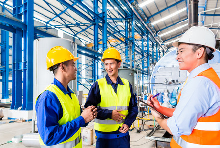 steel factory: Asian factory worker and engineer as team inspecting a machine delivery Stock Photo