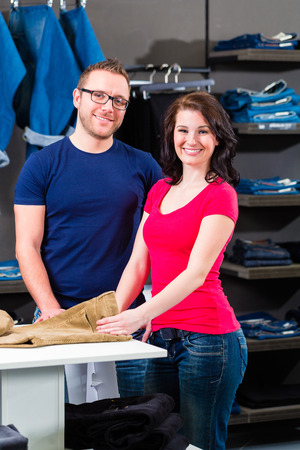 Man and woman buying blue jeans in shop photo