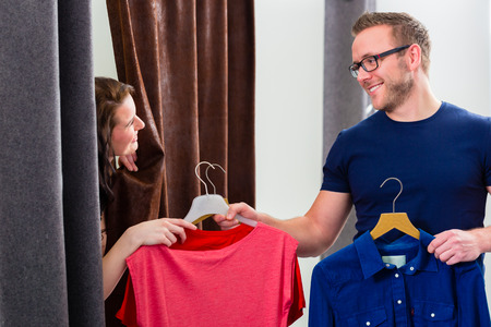 changing clothes: Couple trying clothes in shop changing room Stock Photo