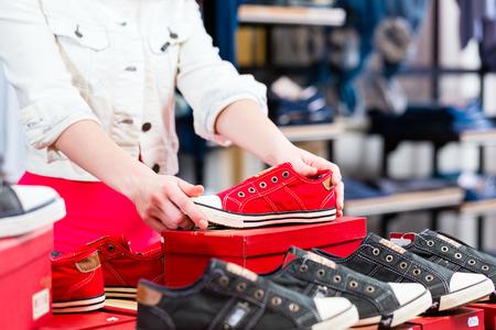 comprando zapatos: Mujer que compra las zapatillas de deporte en la tienda