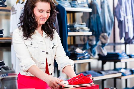 buying shoes: Mujer que compra las zapatillas de deporte en la tienda