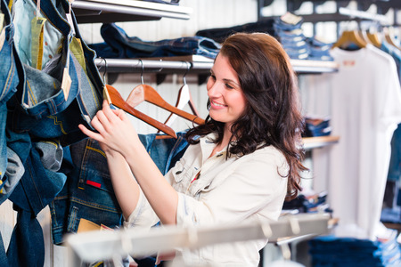 Woman buying blue jeans in shop photo
