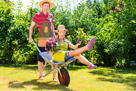 Couple in garden with watering can and barrow photo