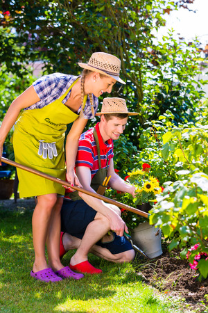 weeding: Couple in garden planting flowers