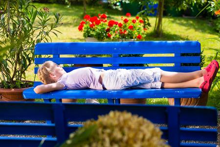 Child in garden lying on bench photo