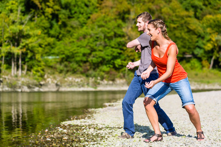 skim: Man and woman skimming stones on river in summer