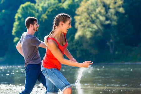 skimming: El hombre y la mujer de skimming piedras en el r�o en verano