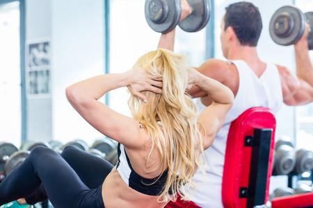 flat stomach: Amigos, hombre y mujer, el levantamiento de pesas en el gimnasio de fitness, ella está haciendo sit-up para vientre plano