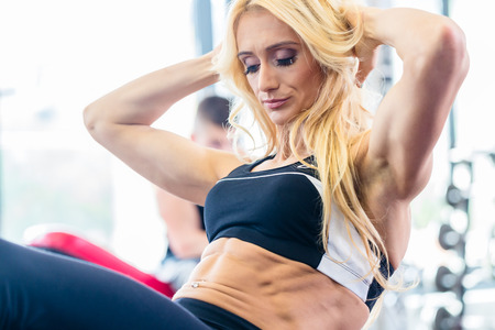 flat stomach: Bodybuilding woman doing sit-up in fitness gym for flat stomach