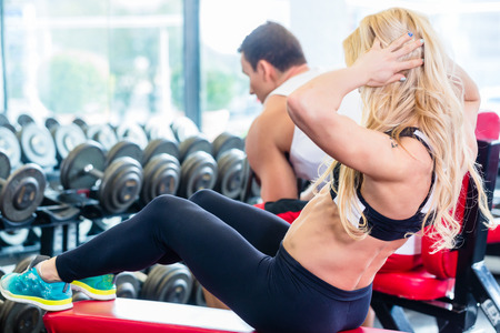 'flat stomach': Friends, man and woman, lifting weights in fitness gym, she is doing sit-up for flat stomach