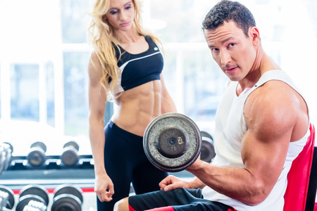 Couple in fitness gym with dumbbells lifting weight as sport, man and woman training together