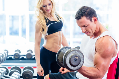 man lifting weights: Couple in fitness gym with dumbbells lifting weight as sport, man and woman training together