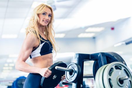 strong arm: Woman taking weights from stand in fitness gym preparing for training