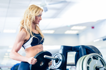 levantar pesas: Mujer que toma un peso de stand en el gimnasio de fitness prepara para el entrenamiento Foto de archivo