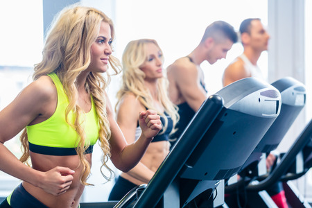 Treadmill group, men and women, exercising in fitness gym photo