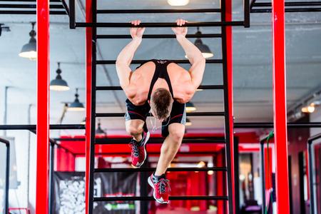 calisthenics: Man at freestyle Calisthenics training in gym on frame