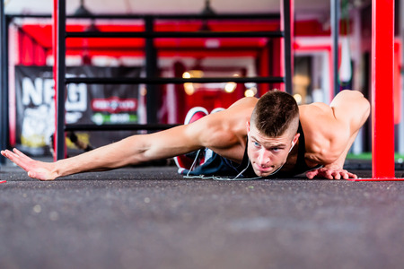 jungle gyms: Man exercising doing push-up on floor of sport fitness gym Stock Photo
