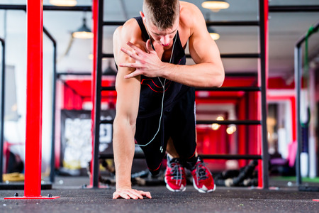 pushup: Man exercising doing push-up on floor of sport fitness gym Stock Photo