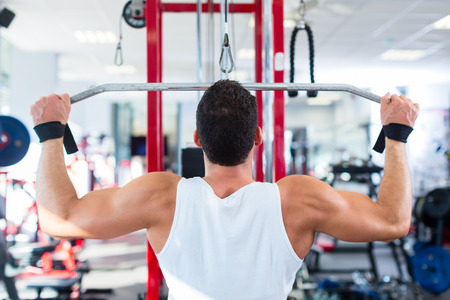 weight machine: Man doing bodybuilding sport by exercising lifting dumbbells in fitness club or gym Stock Photo