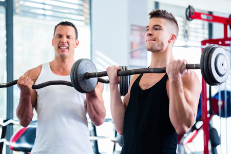 motivating: Friends lifting weights for sport in fitness gym motivating each other with a little competition