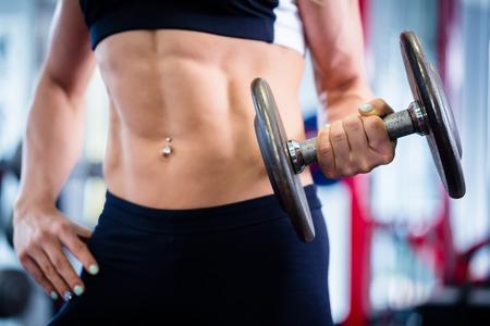 levantando pesas: Mujer de culturista levantamiento de pesas en el gimnasio de fitness