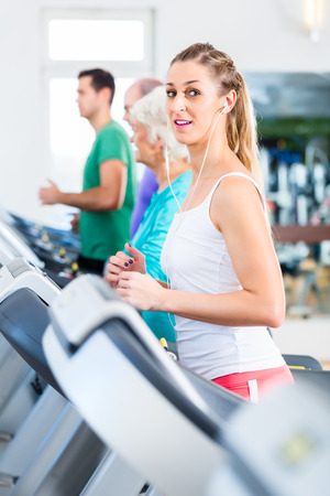 Group with senior and young men and women on treadmill in fitness gym running for sport photo